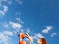Boys Playing Basketball Against Sky