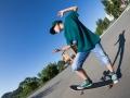 Cheerful boy riding a skateboard on the street.