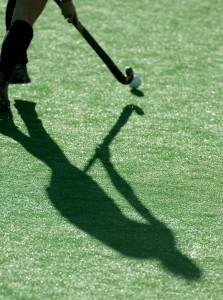 The shadow of a field hockey player as they run down the pitch.