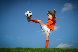 Child kicking playing football