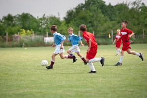kids playing soccer in summer